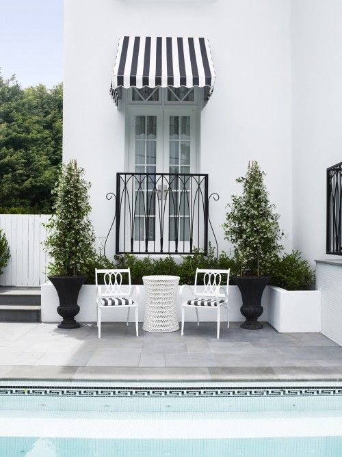 Black And White Greek Key Pool Tile Striped Awning Chairs Topiaries With Matte Planters