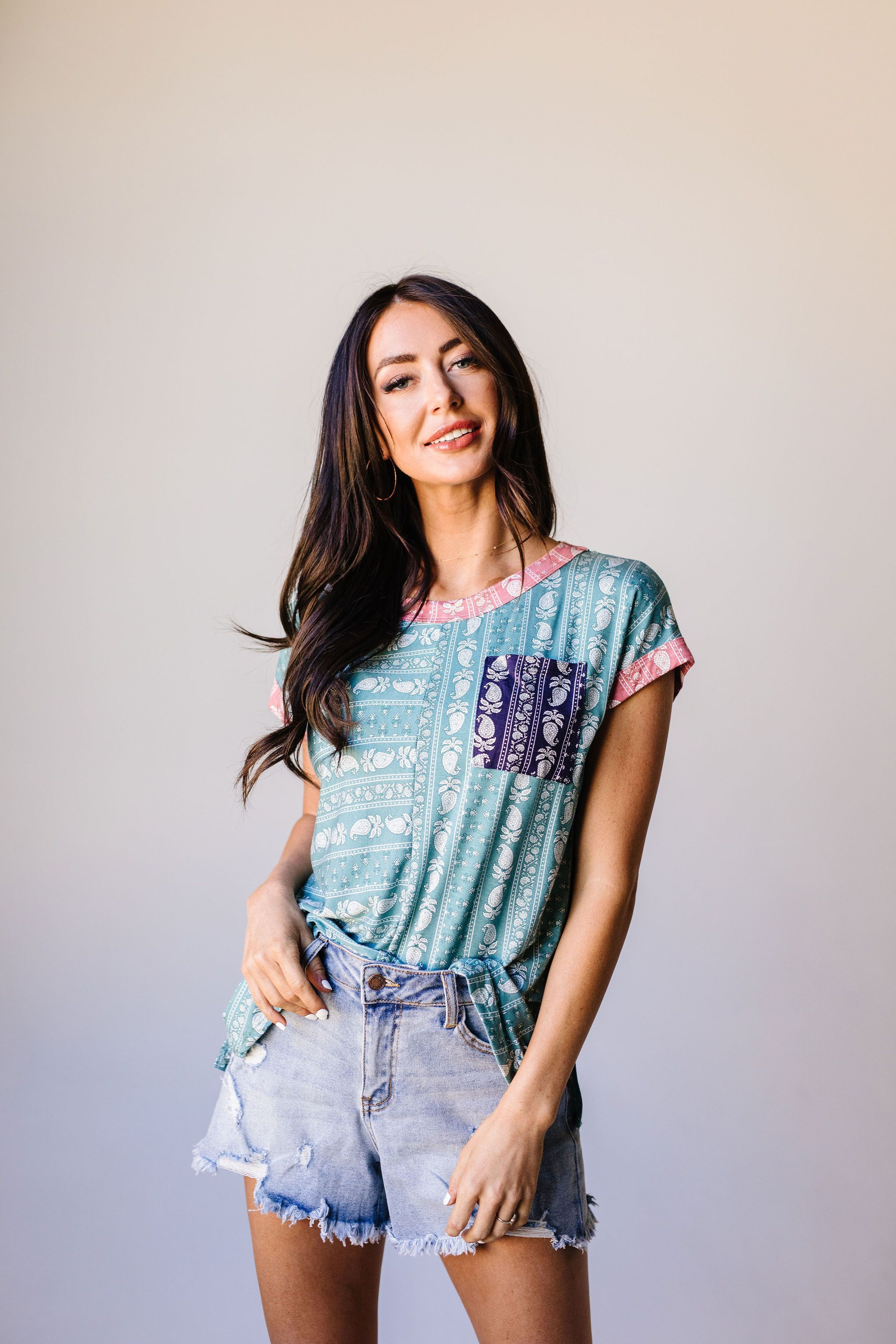 This tee shirt's biggest highlight is the paisley pattern! It's fun, and adds something just a little bit different to your wardrobe. It doesn't end there though; the paisley pattern also has contrasting colors on the cute functional pocket and along the round neckline, and short sleeve hems! LightweightStretchy95% Polyester 5% SpandexRelaxed Fit Made In USA*Measurements listed below are of the actual clothing item* XS: Chest 36