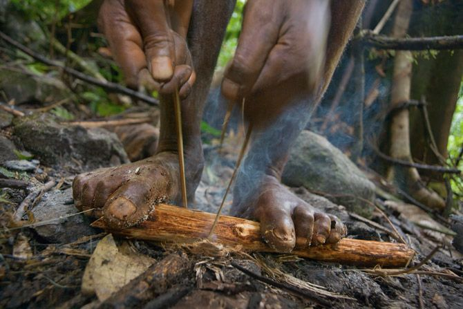"""Gripping a kindling-packed stick with his feet and using a strip of bamboo for friction, a Meakambut man coaxes a cooking fire from soggy terrain. This """"fire saw"""" method is widely practiced throughout Papua New Guinea."""