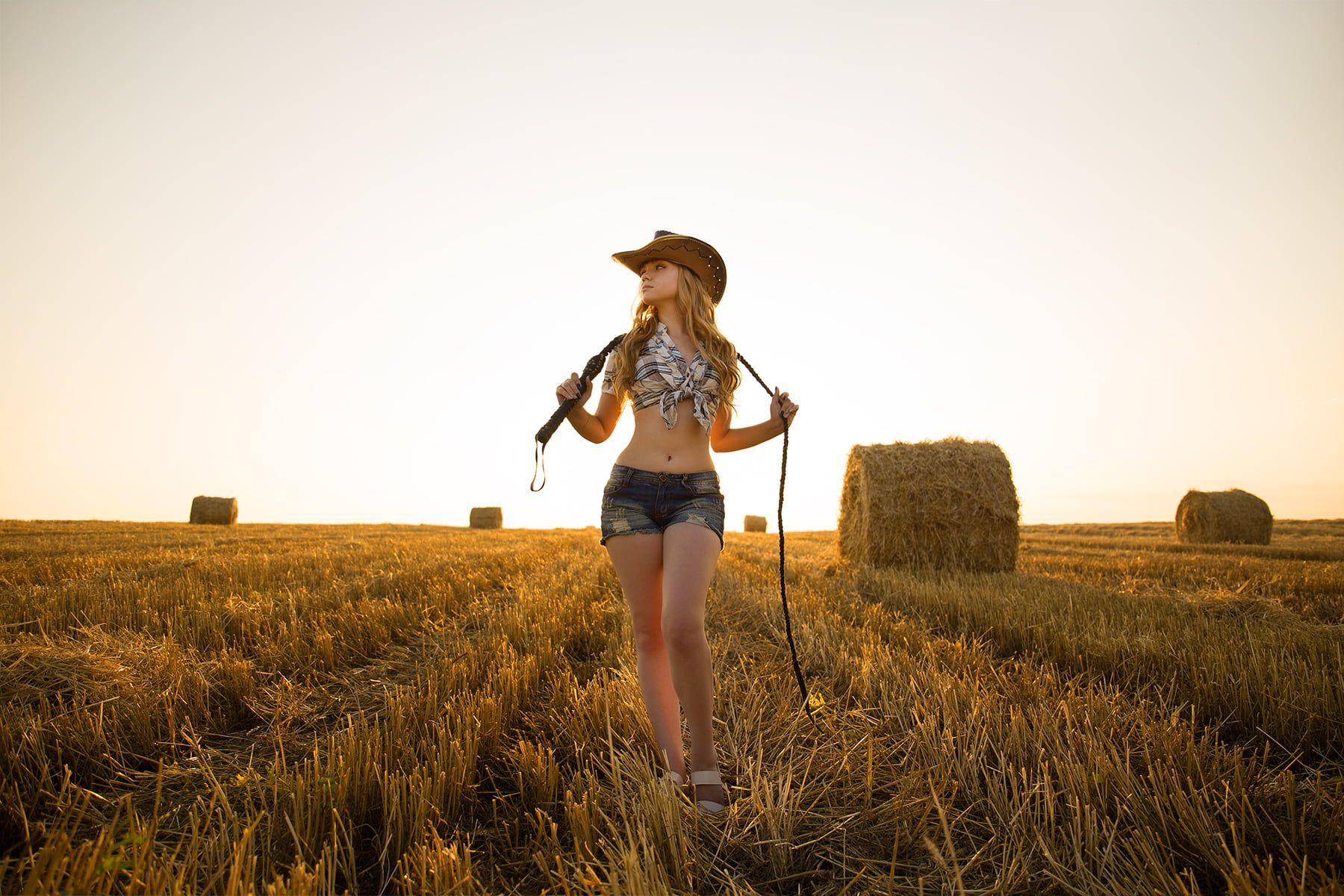 women's white and blue plaid crop top and blue denim short shorts #women #blonde plaid shirt #hay cowboy hats jean shorts #belly women outdoors #cowgirl looking away #720P #wallpaper #hdwallpaper #desktop