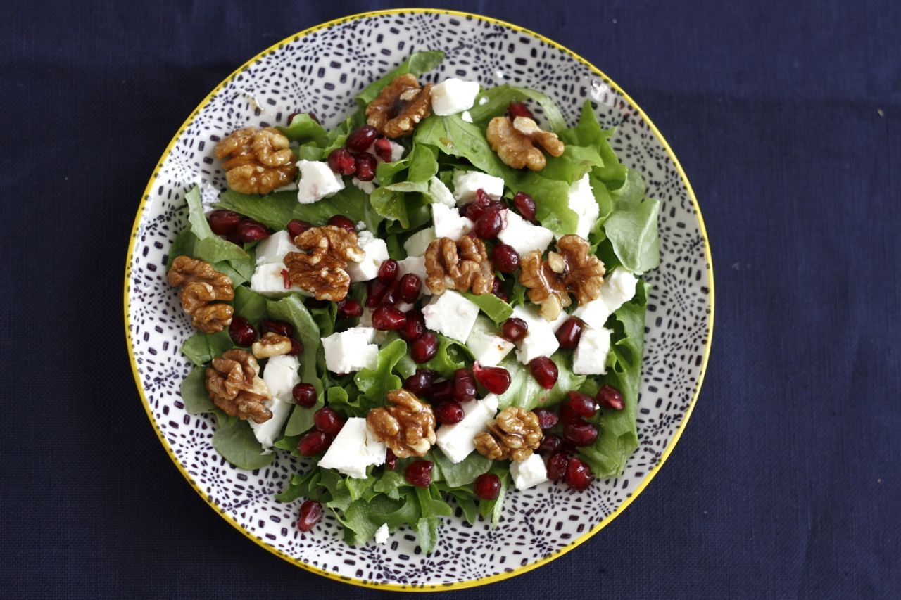 Salad with pomegranate, feta cheese and walnuts.
