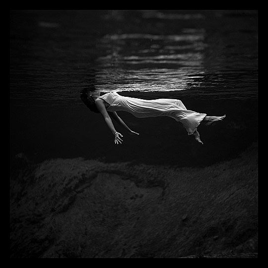 brunette in white dress levitating in the water - b/w photography