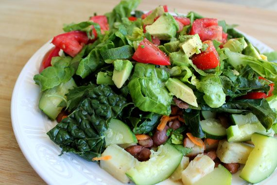 """Above: I call this the """"big pile of food,"""" which is simply a plate FULL of your favorite foods. In this case I had pinto beans, sweet potato, kale and zucchini, topped with tomatoes, lettuce, cilantro, and avocado. No dressings or sauces on this one, just really good quality food to start with."""