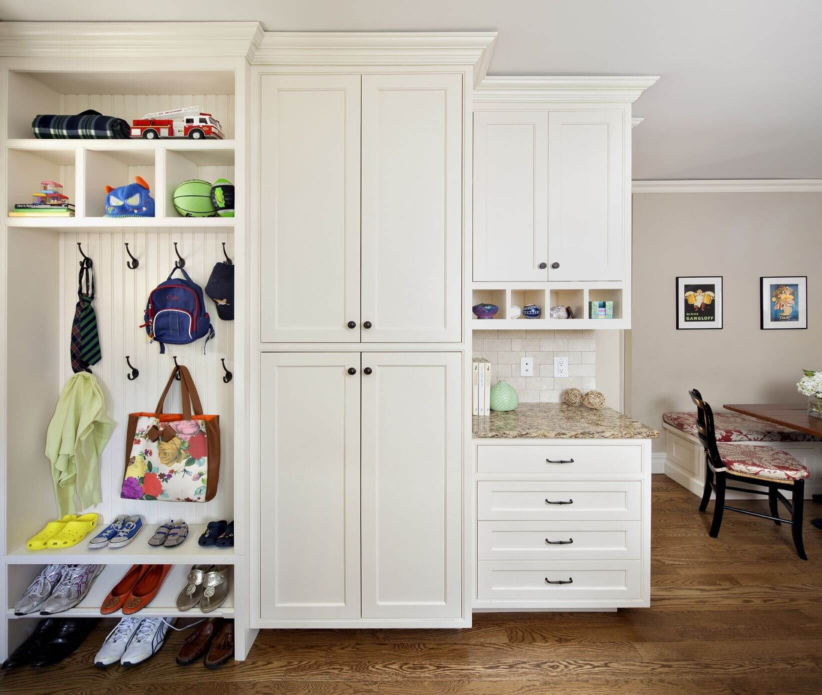 Open mudroom with white storage lockers and granite countertop with ...