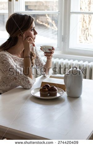 Charming woman sitting by wooden table and drinking coffee