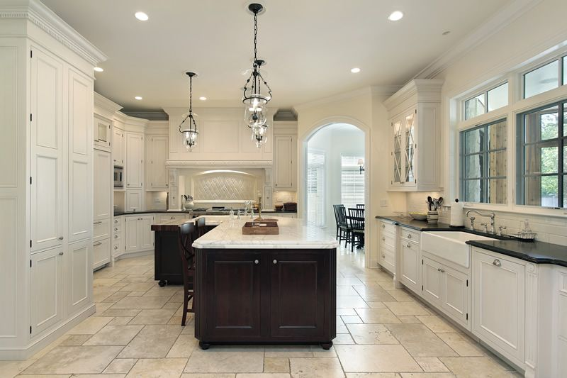 Upscale Kitchen With Marble Counter Island And White Cabinets Paired Dark Countertops
