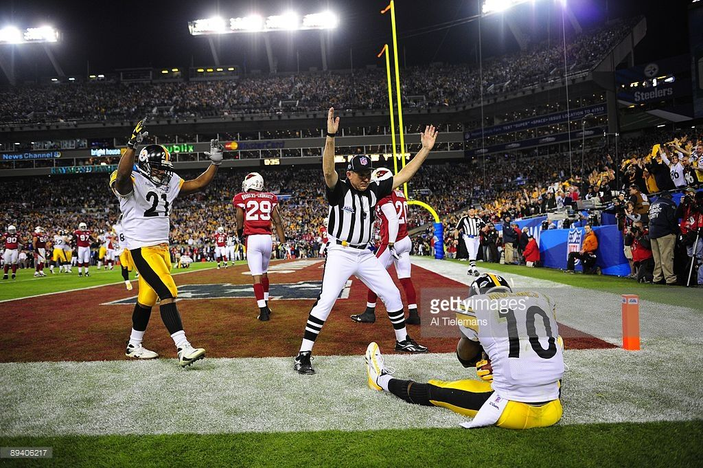 Pittsburgh Steelers Santonio Holmes (10) sitting out of bounds after making game winning touchdown catch vs Arizona Cardinals during 4th quarter. View of Steelers teammate Mewelde Moore (21) and referee, NFL field judge Greg Gautreaux (80), gesturing TD. Sequence. Tampa, FL 2/1/2009