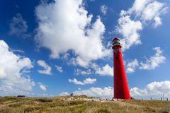 Rotes Leuchtturm oer blauer Himmel Stockbilder