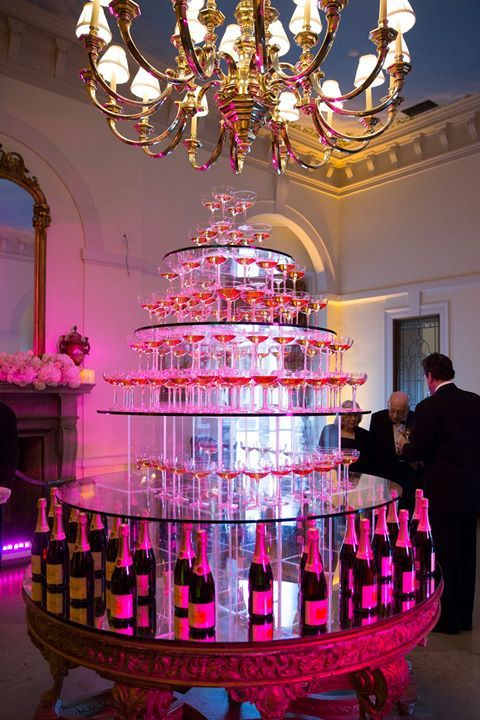Striking pink champagne tower for an afterparty ~ https://www.insideweddings.com/weddings/regal-outdoor-ceremony-ballroom-reception-at-oheka-castle-in-ny/821/