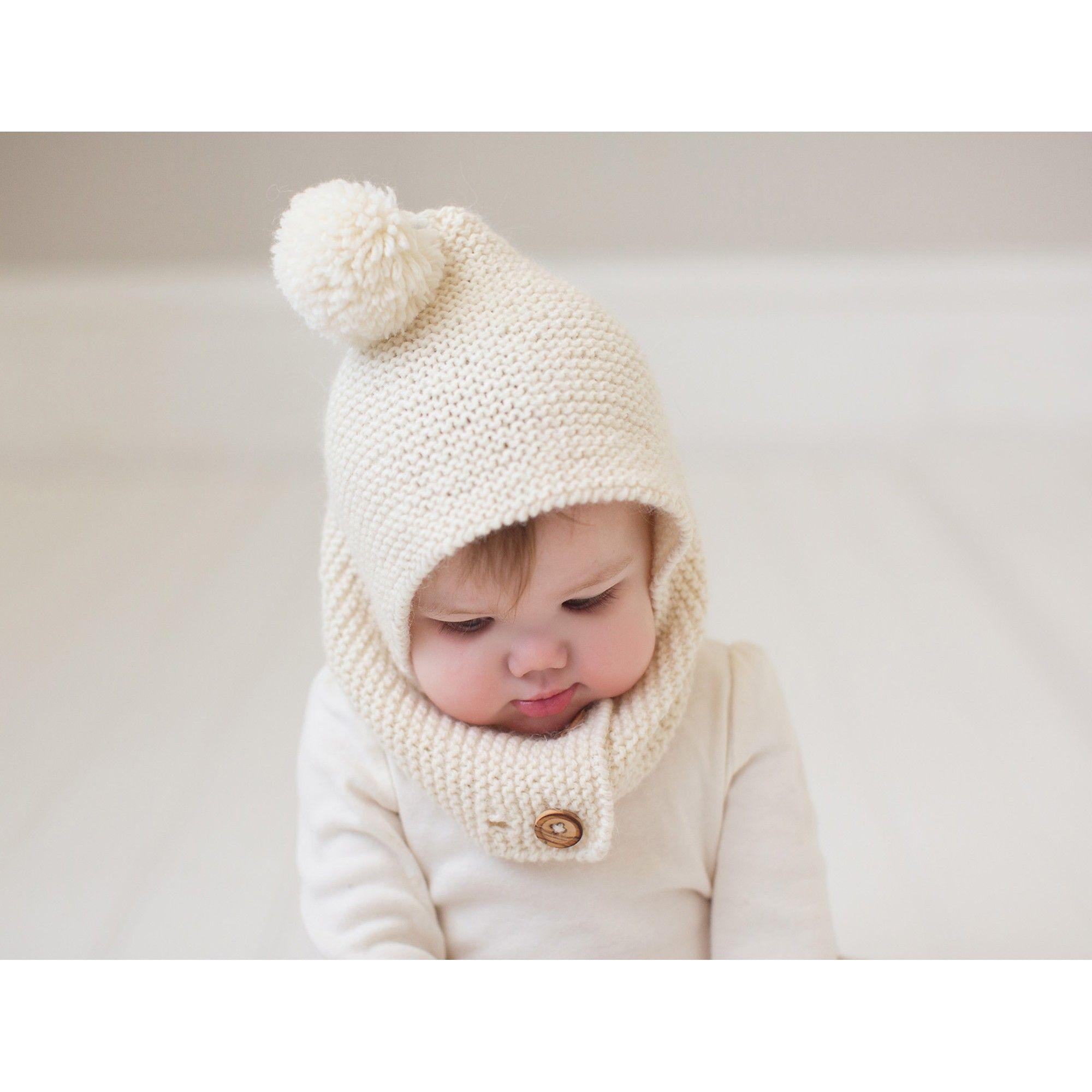 18242c03762 Cagoule style capuche pour bébé coloris écru avec pompon. Parfaitement  ajustable à la tête de l enfant grâce aux 2 rangées de boutonnières qui  permettent de ...