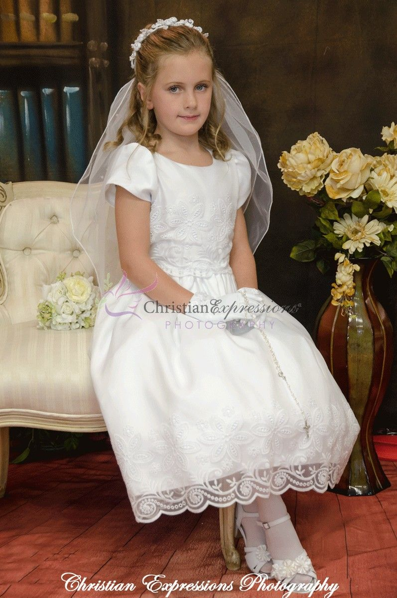 0b650f4cf3f Short sleeve matte satin tea length first communion dress with eyelet  floral design with organza overlay. Zipper closure with organza bow tie  back.