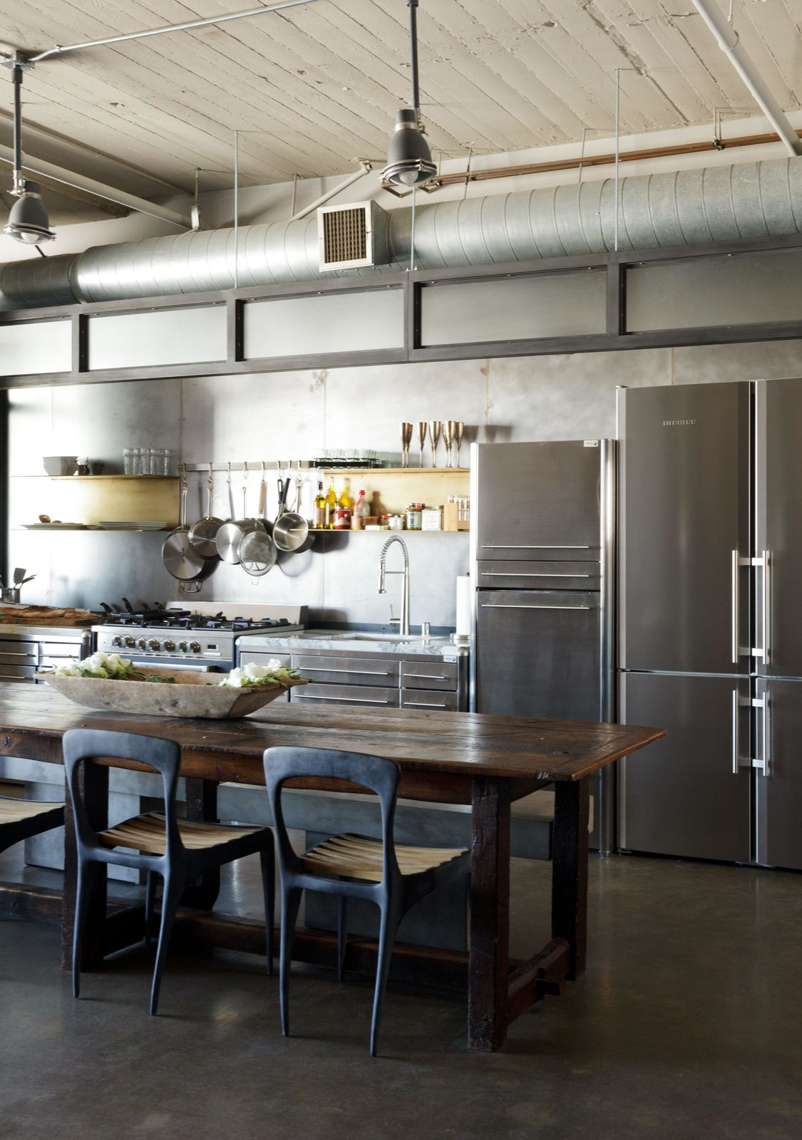 In a loft renovated by designer andrea michaelson a liebherr refrigerator blends in with stainless steel cabinets from fagor featuring calacatta paonazzo