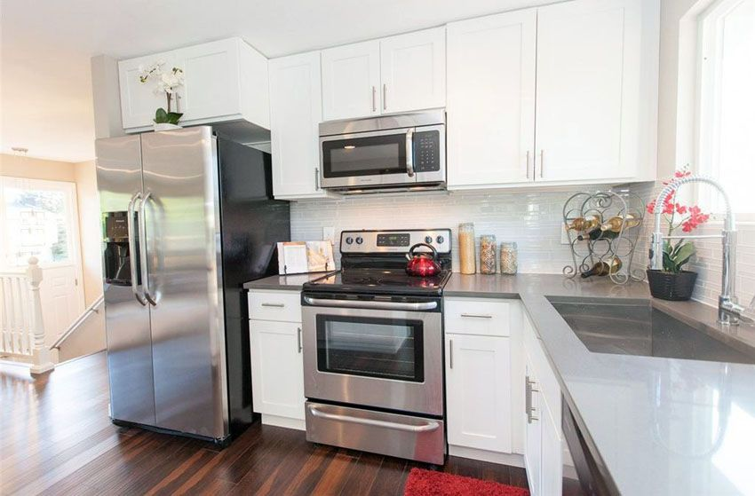 Small Kitchen With White Thermofoil Cabinets And Gray Quartz