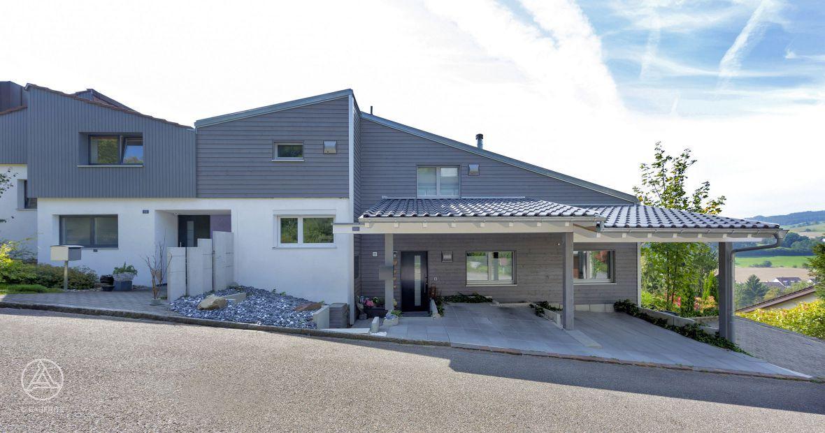 Versetzter Anbau mit großem Vordach im Eingangsbereich, einem Doppel-Carport, Veranda und großen Pfosten-Riegel-Fenstern – Baufritz Anbau Schmid.