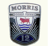 Morris 12. This large badge is much more ornate than the other shield shaped badges of the period having ears of wheat and diagonal 'rays' emanating from the 12. Marked J FRAY Ltd, B'HAM. It measures 48mm x 62mm
