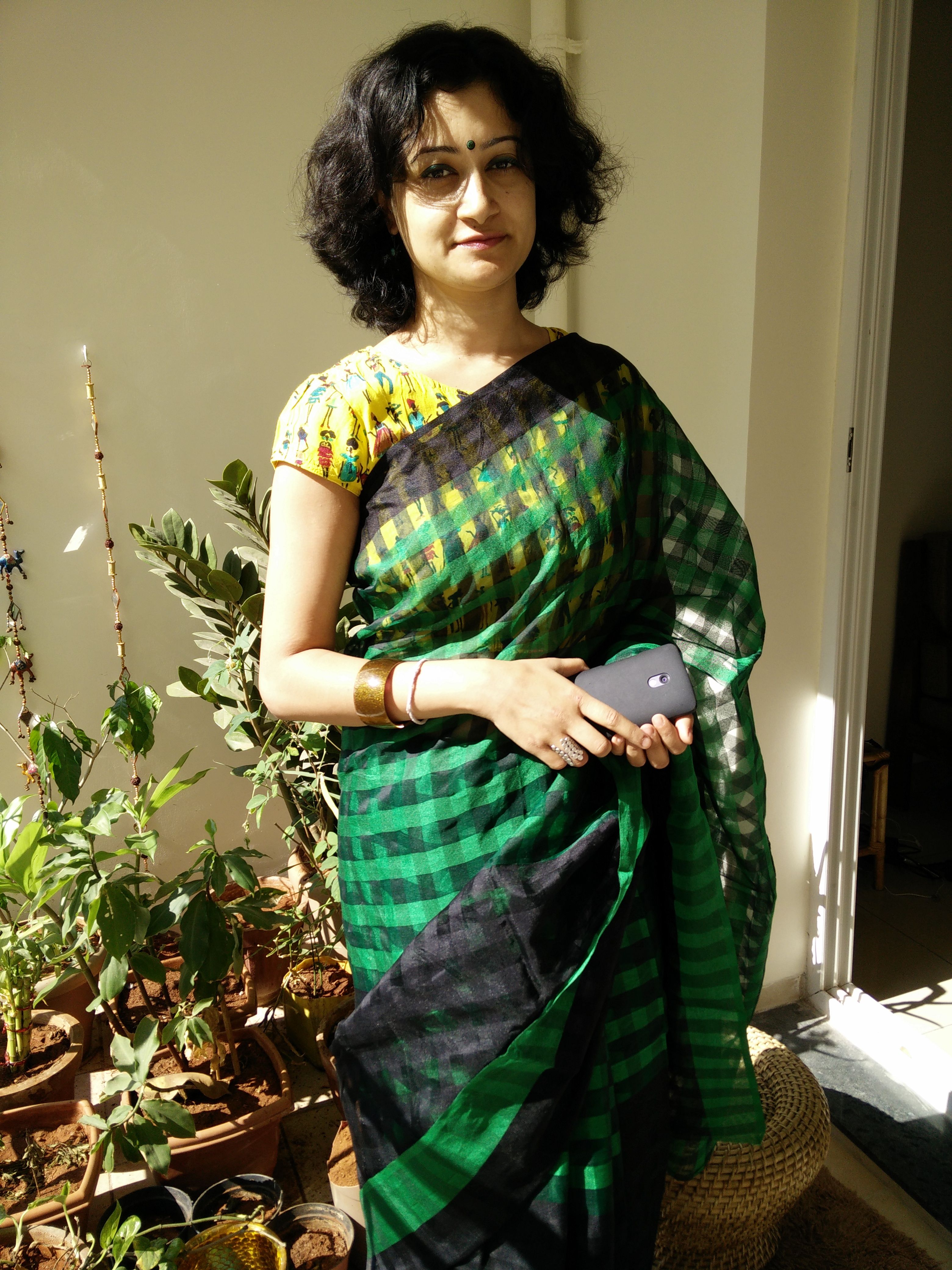 A chequered green and black saree with a contrasting yellow cropped top...The cropped top is fun as it has figurines in it.