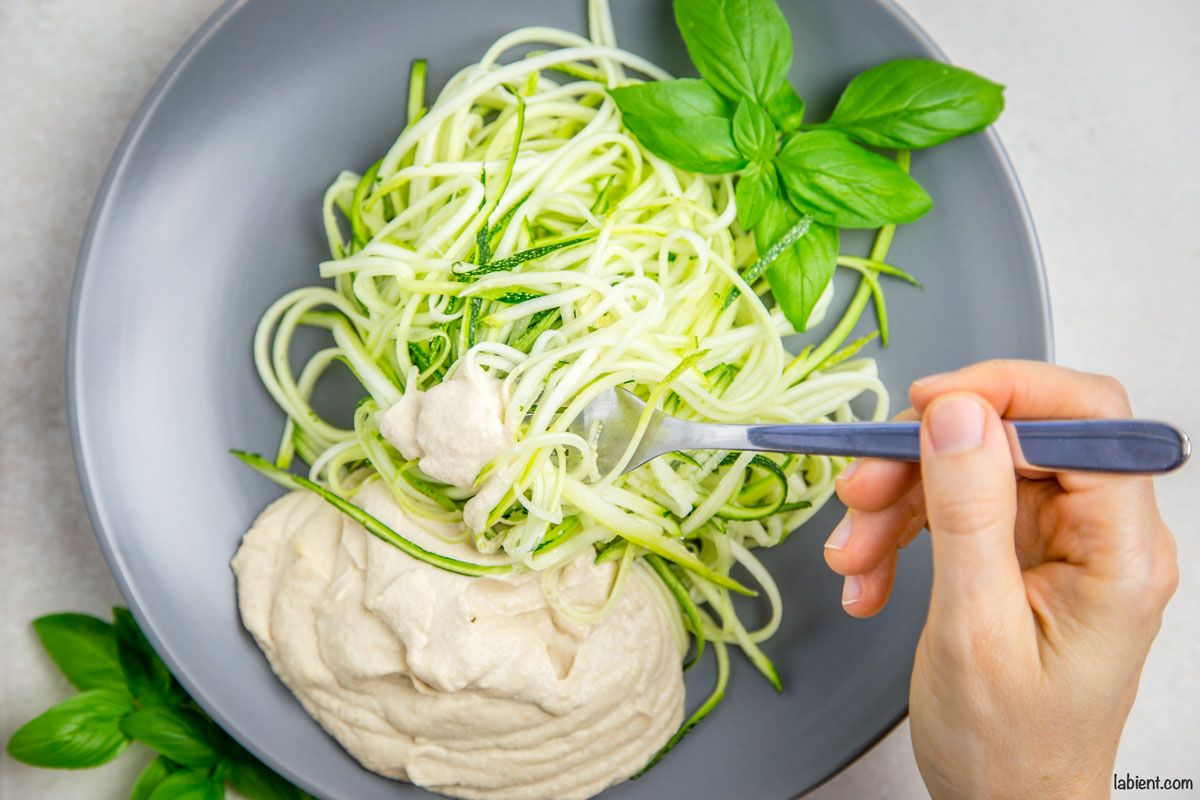 Healthy zucchini noodles with creamy cashew sauce recipe is both yummy and easy to make. You'll get both the basic recipe and a ton of variations. Serve it raw or cooked: great for both summer and winter months!