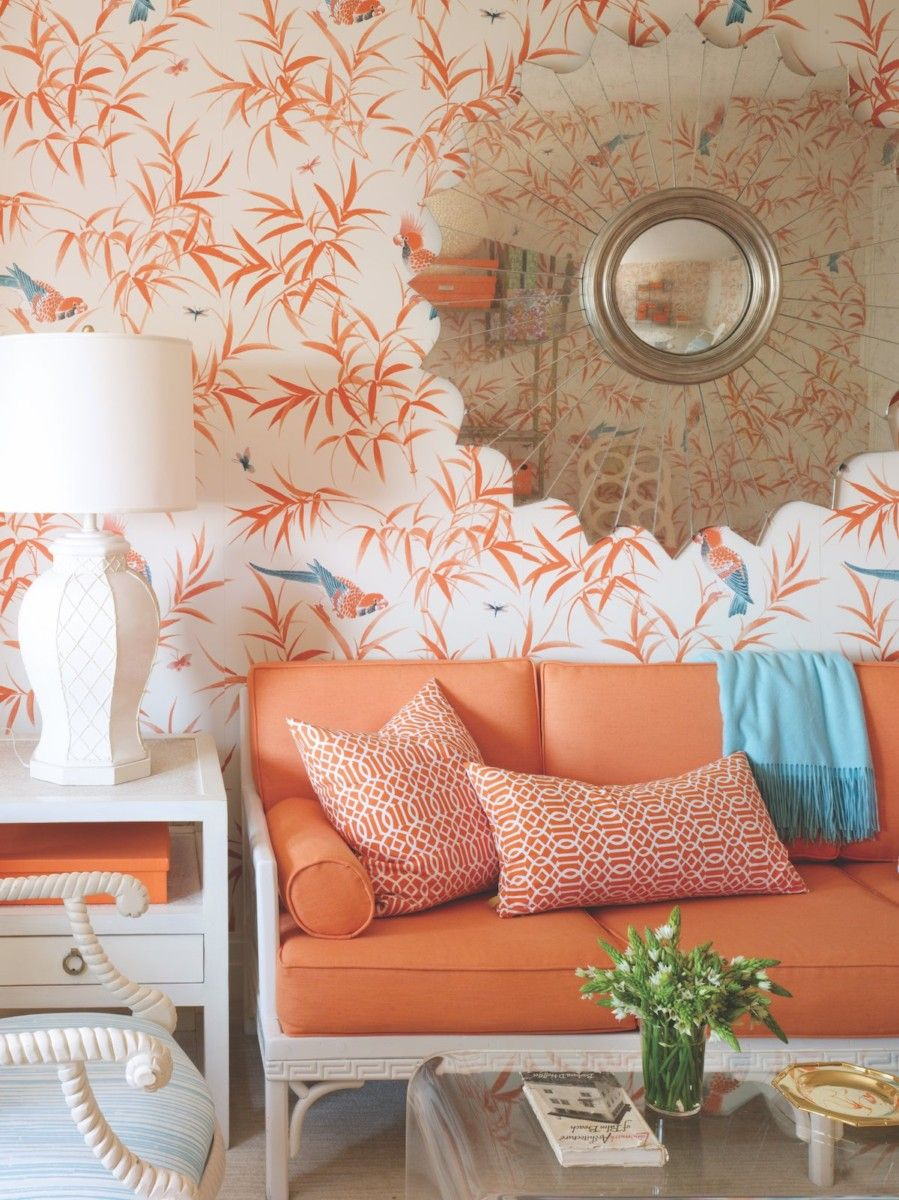 Solid orange upholstery on a vintage bamboo sofa offers a visual landing spot against a patterned wall. Photo by Annie Schlechter