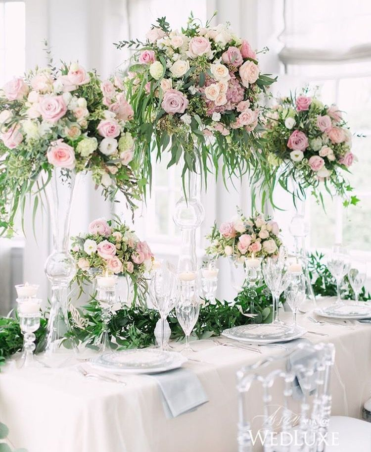 We really like this design for our tall reception table arrangements in the gold holder. We love all of the greenery and the light blush and soft rose colors. We would like to add more white and ivory flowers.