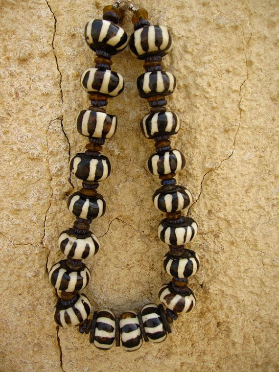 """African Trade Bead Bone Zebra Collar These authentic bone beads are hand carved from boiled, bleached cow bone, polished, and buffed smooth making each bead unique. The Zebra design on these brown and white bone beads is created by the dying method known as """"batik"""", which is a wax relief process."""