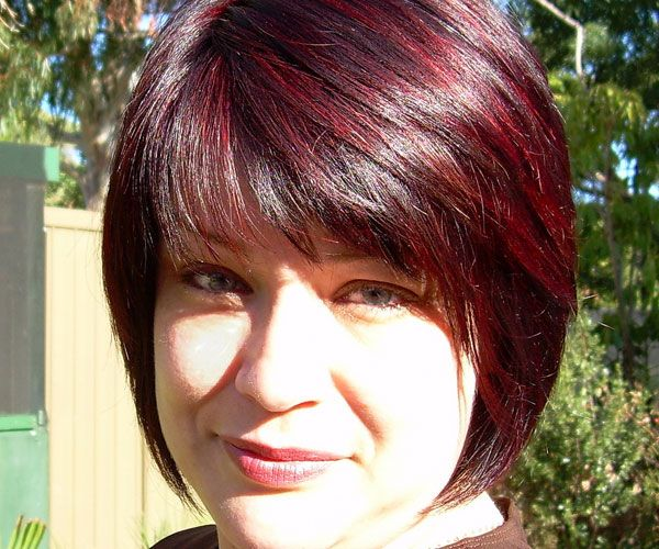 The Silky Black Bob Cut Hairstyle With Red Highlights Has Pointed