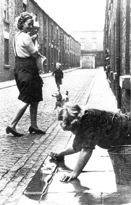 A mum stops to chat to a neighbour mopping the flags outside the front of her house in 1950's Blackburn