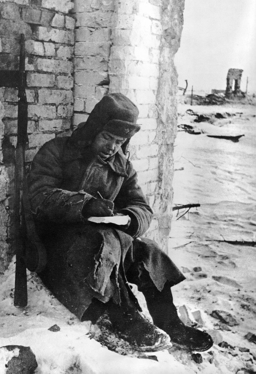 Soviet soldier, sitting in the ruins of Stalingrad, writes a letter upon the end of the battle, January 1943.