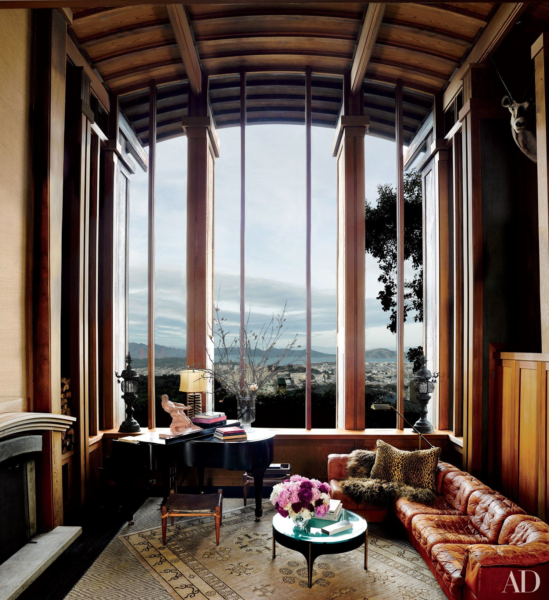 This San Francisco residence enjoys expansive city views from the 27-foot-tall window in the great room. Ken Fulk furnished the space with a vintage de Sede sectional sofa and a pillow in a Ralph Lauren Home leopard print; the 1910 Steinway was originally owned by pianist Alfred Cortot.