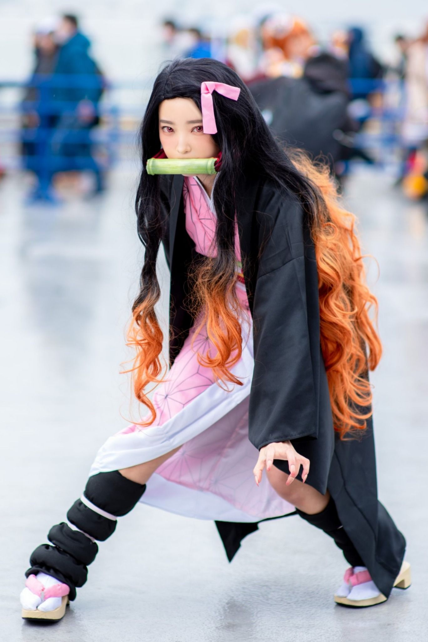 This Demon Slayer Nezuko Kamado cosplayer is in a fierce stance! The cute Nezuko Kamado looks badass, mad, and ready to fight in this full Kimetsu no Yaiba costume. Complete with the pink kimono, the bamboo muzzle, the leg guards, the long black-to-orange hair, the pink nails, and the Japanese Geta sandals, this Nezuko Kamado cosplay is perfect! #KimetsuNoYaiba #DemonSlayer #Nezuko #NezukoKamado #TanjirouKamado #KamadoNezuko #Cosplay #Anime