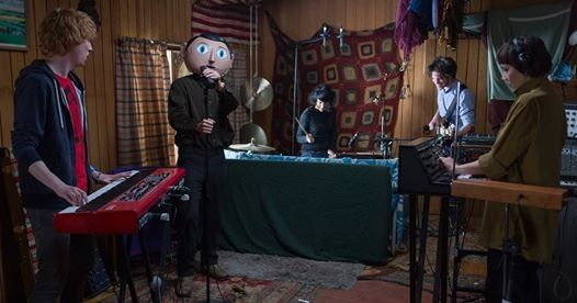 """""""Frank"""" is an inspired character, and Fassbender, playing nearly all his scenes with the mask, acting almost entirely with his arms and voice, brings him to life. Whether Frank is instructing his musicians to squawk like birds or describing his facial expressions beneath the mask or writing a song about a carpet strand, Frank could never carry the this risky movie were he not embodied by a superb actor. ~ Anita Katz"""