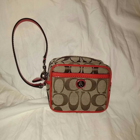 Coach Wristlet. New without tags. Orange/red coach wristlet. 5 1/2 long 2 wide 3 1/2 high.  Can fit phone, money, keys and money. Brand new never used. Coach Bags Clutches & Wristlets