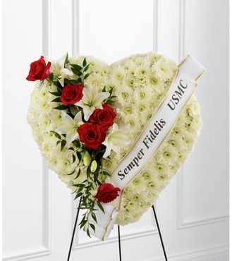 """A pearly white heart consisting of chrysanthemums is accented with an arrangement of red roses, white Asiatic lilies and lush greens, as well as, a white banner that reads, """"Semper Fidelis USMC,"""" to create an incredible presentation at their final memorial service. Displayed on a wire easel.  Approximately 24""""h x 24""""w"""