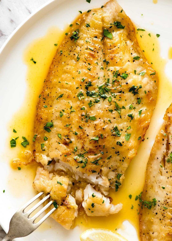 Overhead photo of a crispy pan fried fish fillet drizzled with Lemon Butter Sauce and sprinkled wit