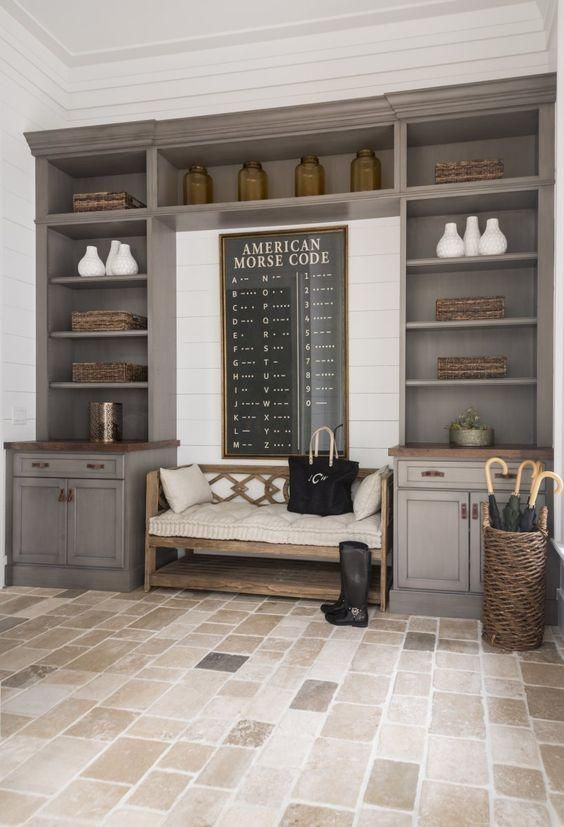 Classic gray tiled mudroom with built-in floor to ceiling open shelves, cabinets, and drawers topped with butcher block counters, and a nook with upholstered wood and cream linen bench, wicker basket for umbrellas and mixed stone tiled flooring.