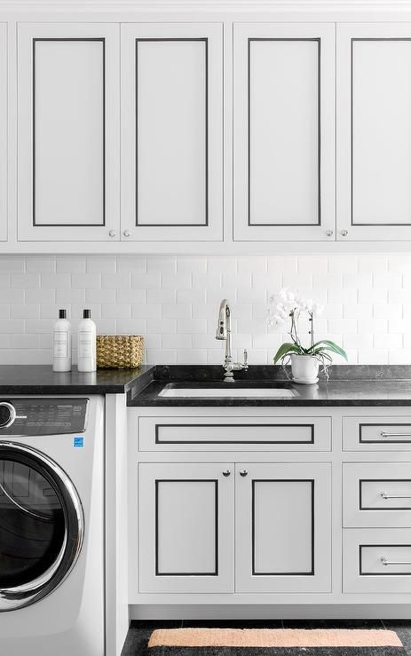 White laundry room cabinets with black trim to accent ...