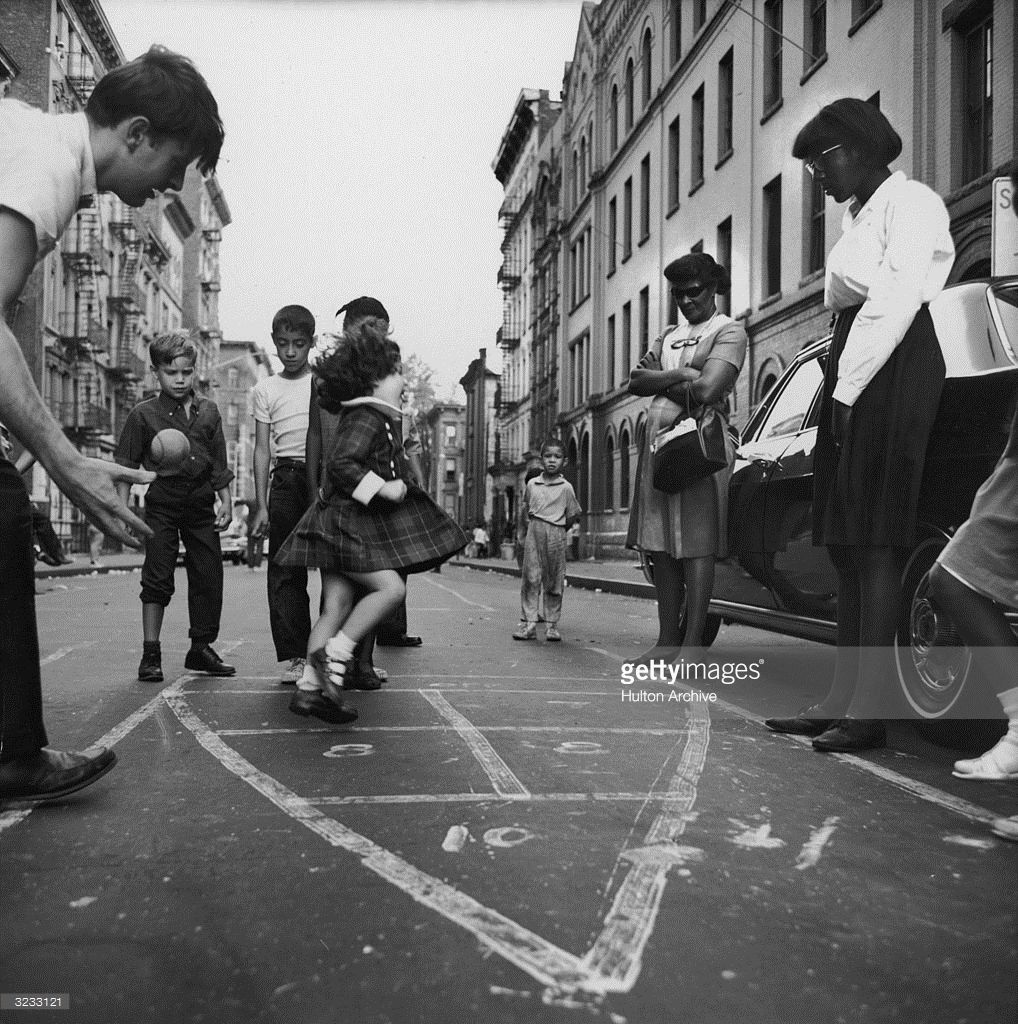 A view of children playing hopscotch in the street in Spanish Harlem, New York City.