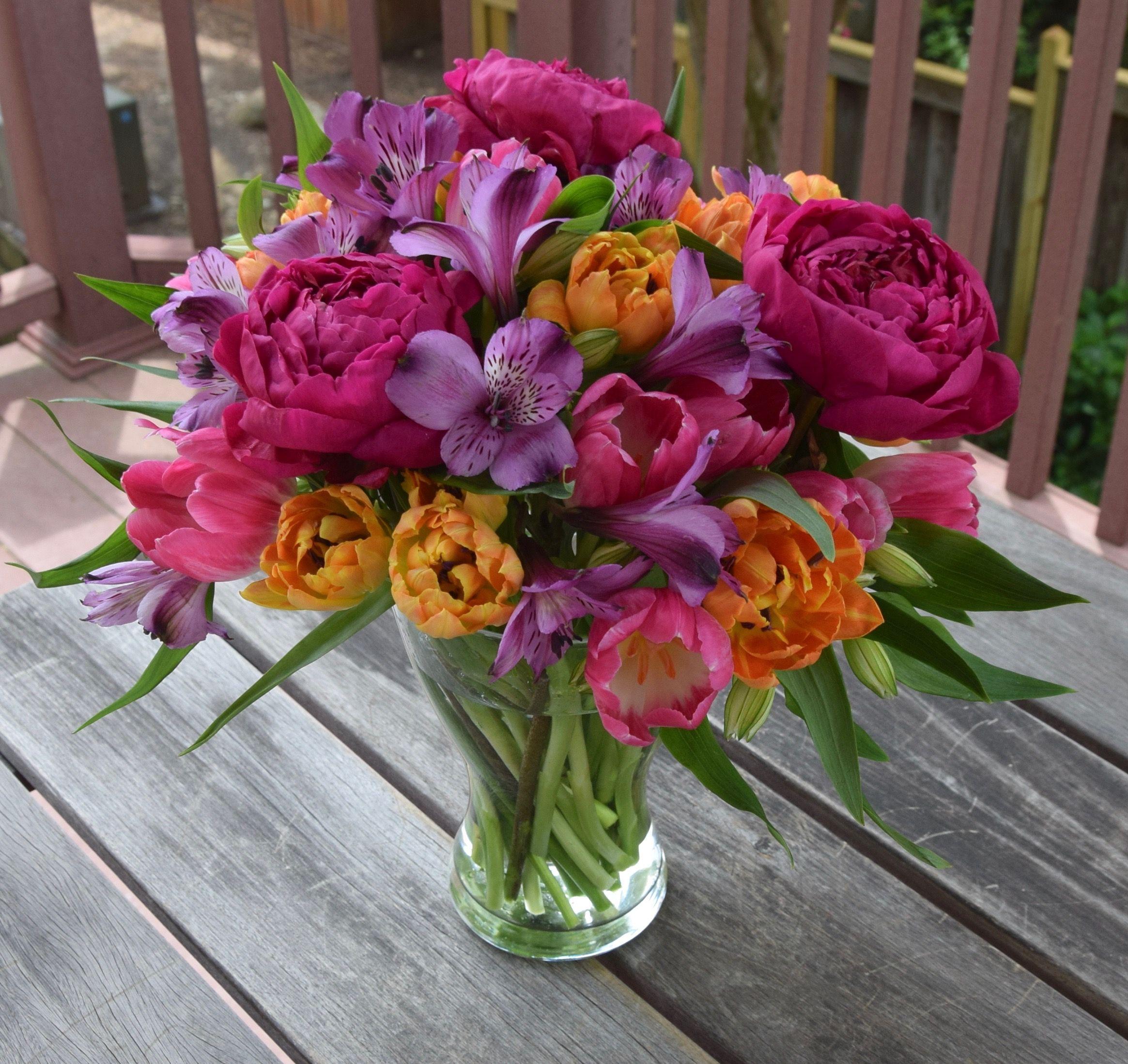 Flower arrangement in jewel tones with peonies tulips