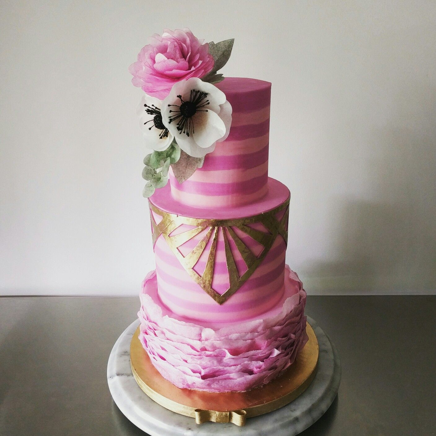 A bold magenta and pink wedding cake with gold deco details and ...