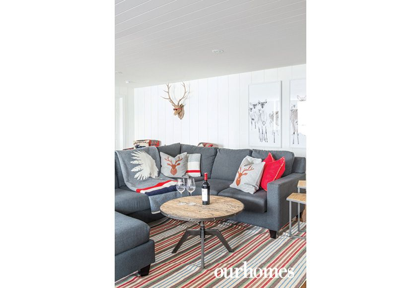 A grey sectional sofa and reclaimed wood-and-steel tables furnish the man cave's TV viewing space.  http://www.ourhomes.ca/articles/build/article/whitewashed-weekender-ripe-with-rustic-chandeliers