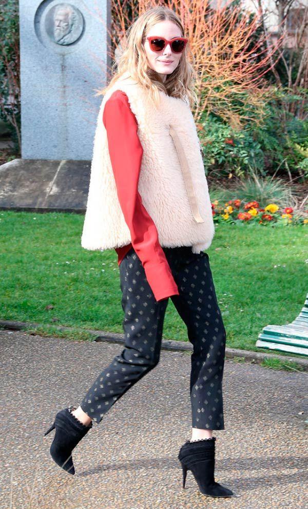 Street style look com colete, blusa vermelha e calça estampada.