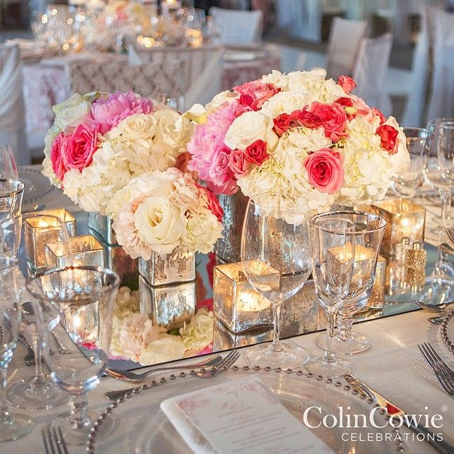 Arrangements of peonies hydrangeas and roses in mercury glass vessels sit atop a mirrored surface to create a glamorous feel. @teamcowieproductions #colincowie #CCCelebration #teamcowie #wedding #tabledecor #peony #hydrangea #candlescape #centerpiece #flowers #mirror via @angela4design