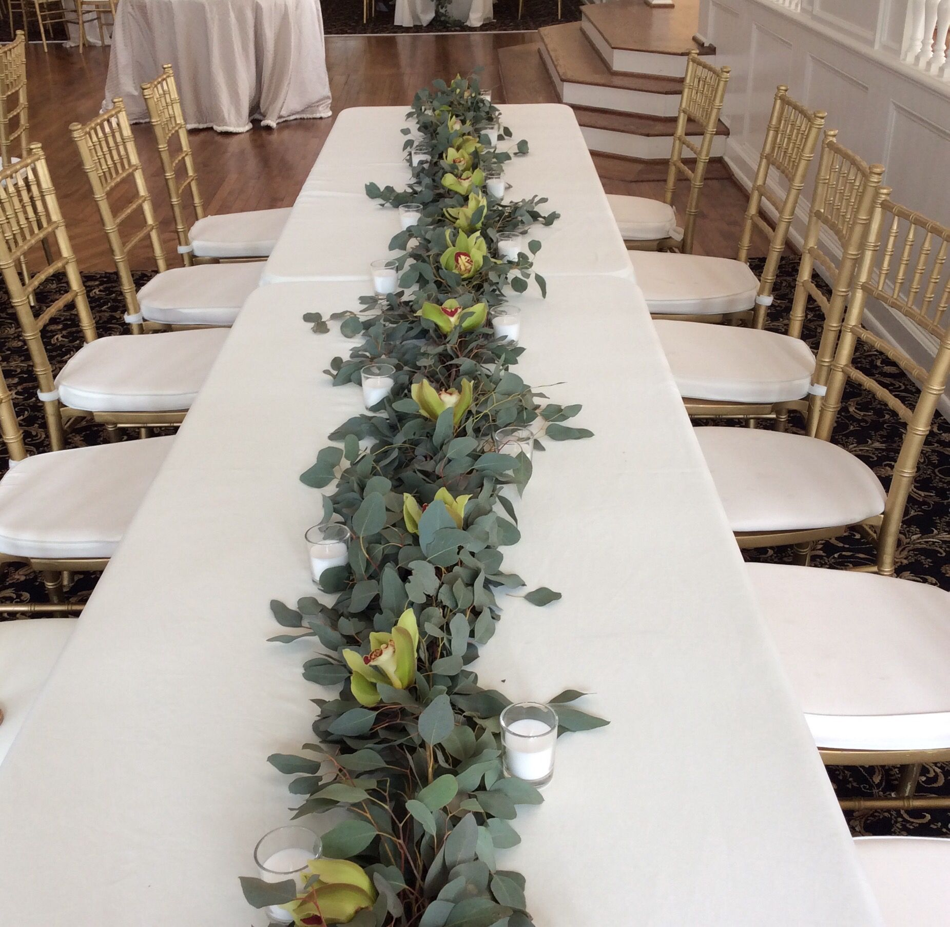 Family table with a eucalyptus garland and green cymbidium orchids
