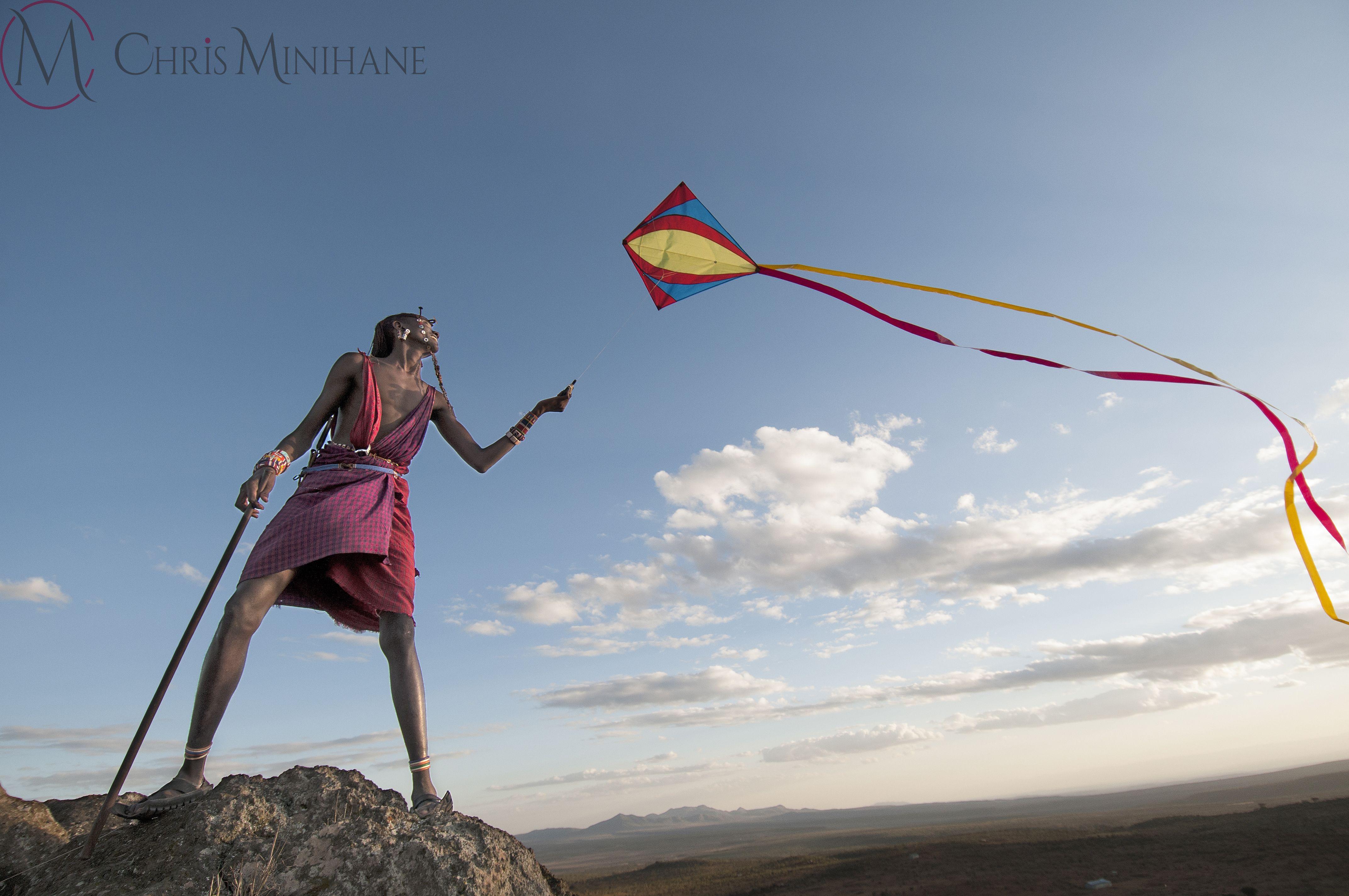 A Maasai Warrior flies a kite.