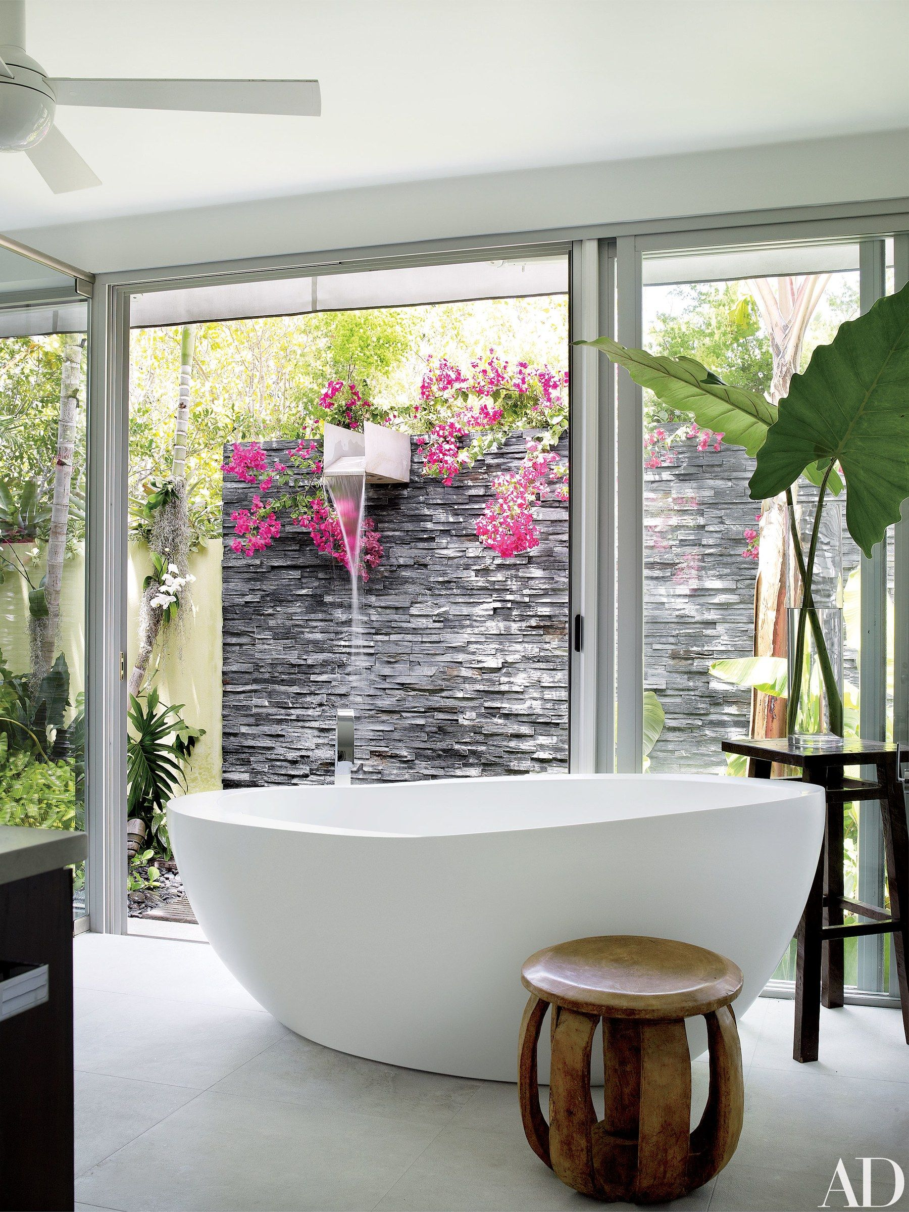 A Waterworks tub in the master bath faces a slate-walled waterfall ...