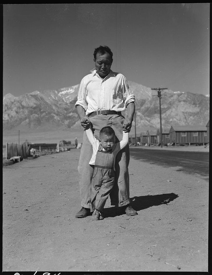 A grandfather teaches his grandson how to walk at Manzanar Japanese-American internment camp, 1942. Photograph by Dorothea Lange.