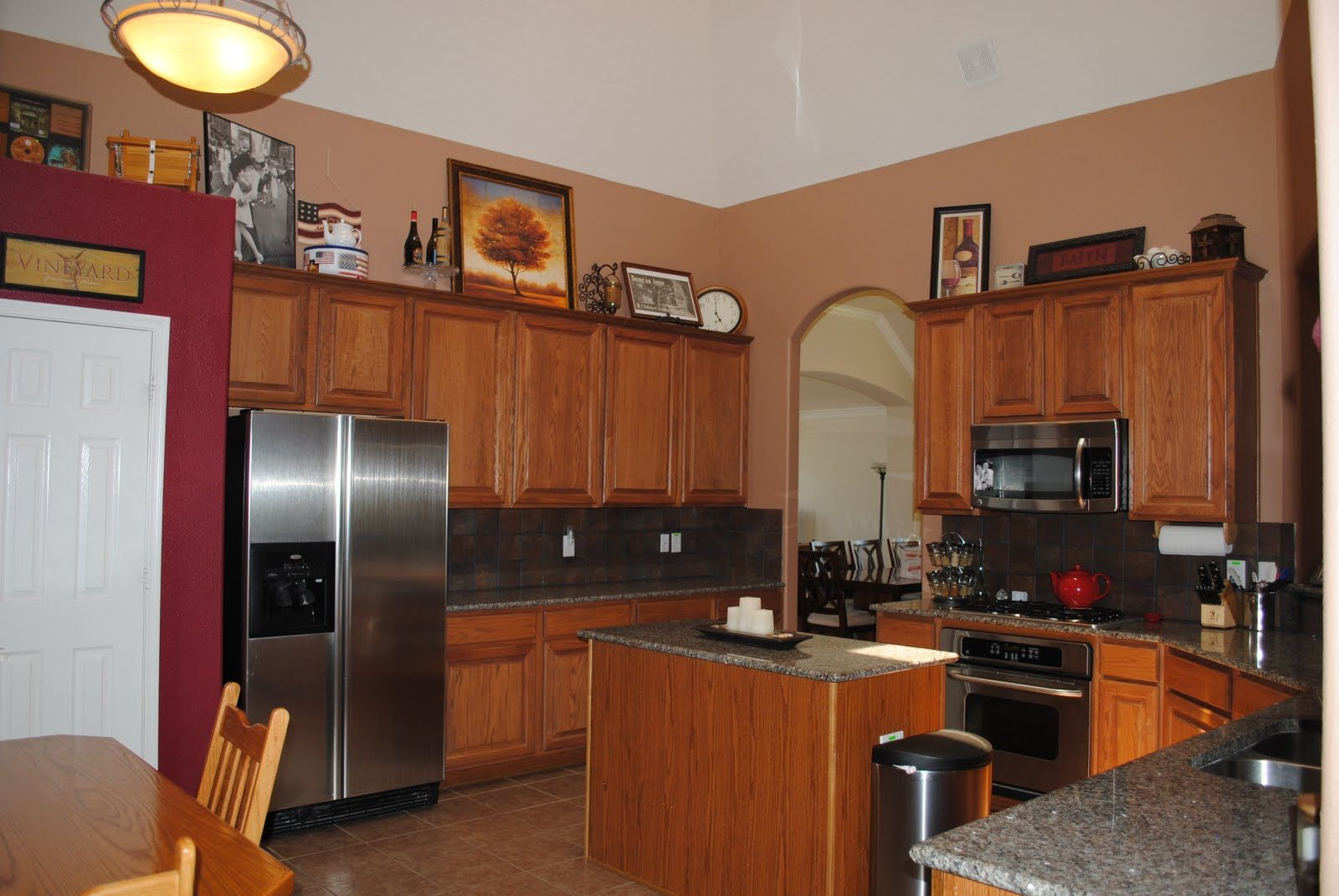 Red accent wall in kitchen with brown cabinets google for What color to paint kitchen