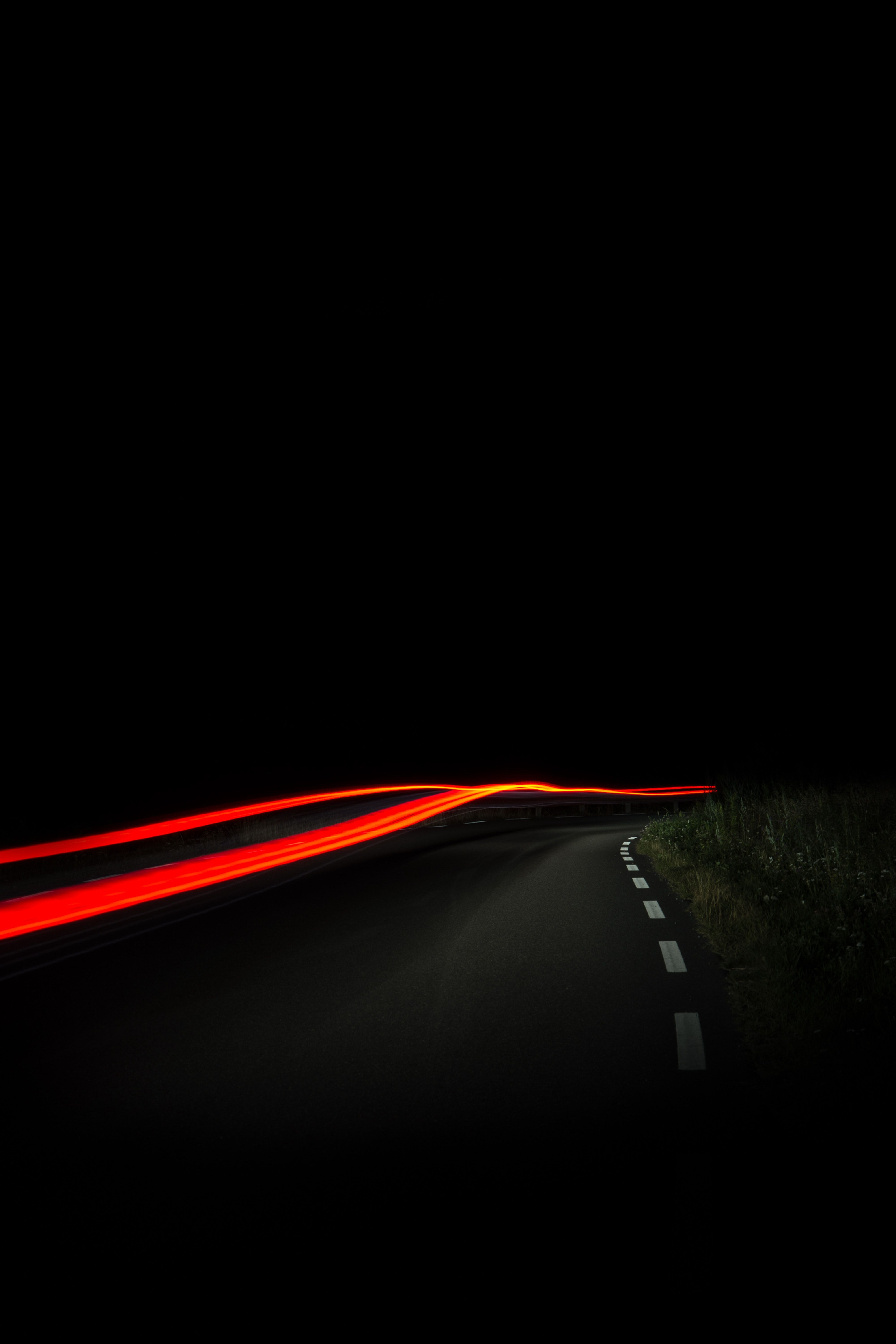 A blurry nighttime shot of a road in Åsa, with red car