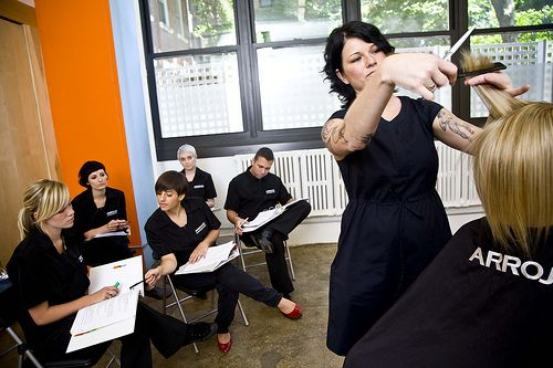 this is a professional hair stylist teaching trainees in her class on how to cut hair - Professional Hair Stylist