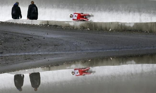 Course workers look at Switzerland's Martina Koch speeding down the track during the women's luge World Cup at the 'Sanki' sliding center in the winter sport resort of Rosa Khutor, a venue for the Sochi 2014 Winter Olympics near Sochi February 22, 2013. Although many complexes and venues in the Black Sea resort of Sochi mostly resemble building sites that are still under construction, there is nothing to suggest any concern over readiness. Construction will be completed by August 2013…