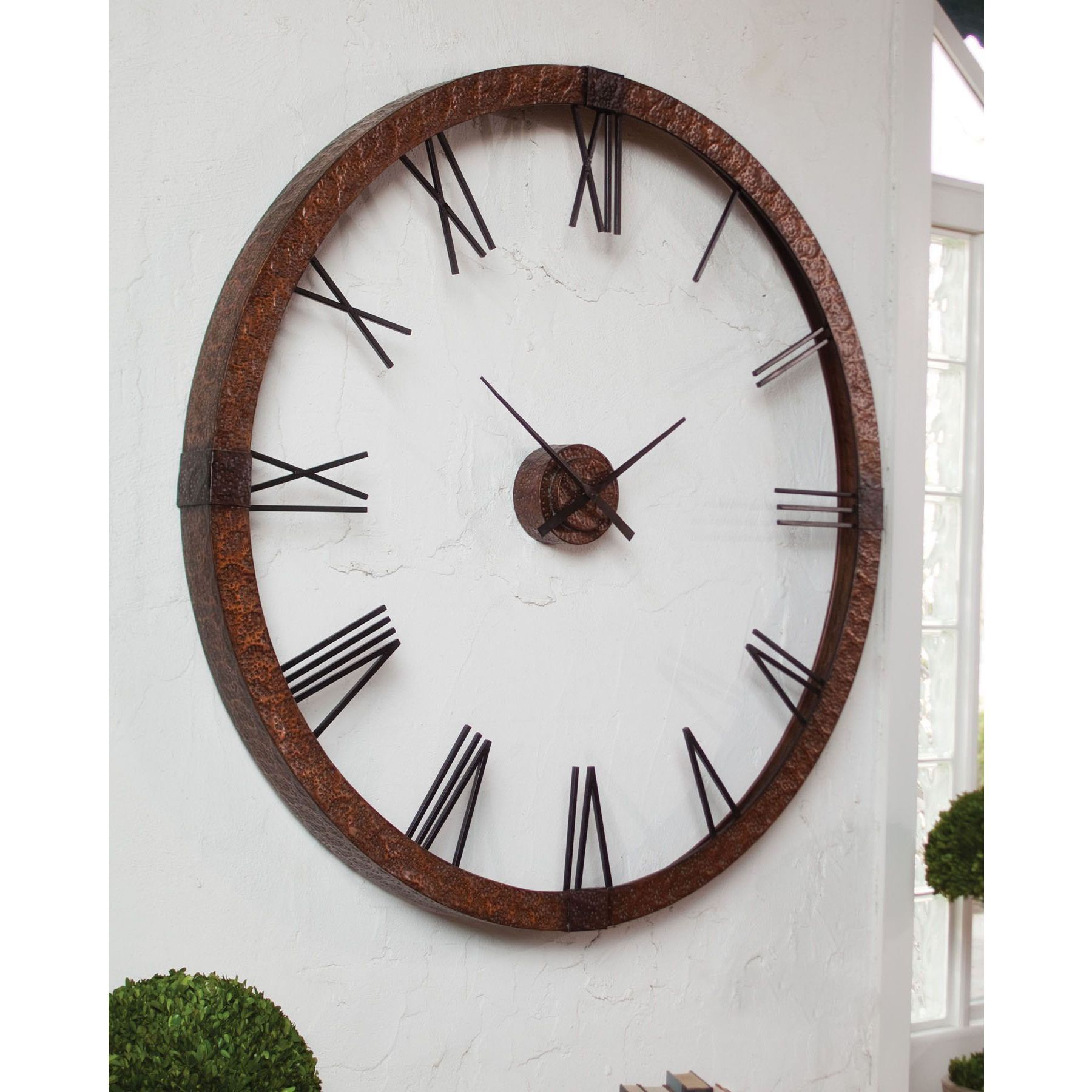 This oversized clock features hammered copper sheeting with a light gray wash and aged black details. Center hands movement is separate from the outside frame. Uses one AA battery. Some assembly required.